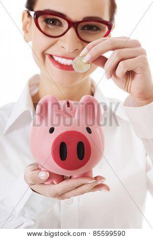 Woman in eyewear putting money to piggybank.