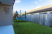 picture of swingset  - Kids trampoline and play set in small green backyard - JPG