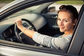 stock photo of driving  - Pretty young woman driving her new car   - JPG