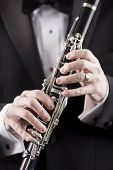 stock photo of clarinet  - hands of man in tuxedo holding clarinet - JPG