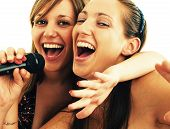 stock photo of singing  - Two young girls singing on a karaoke - JPG