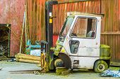 stock photo of wheel loader  - Old abandoned fork lift with missing wheel and supported by stack of wood - JPG