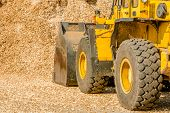pic of wheel loader  - Yellow front loader with bucket down scooping wood chips for biofuel - JPG