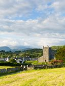 picture of church-of-england  - Hawkshead Lake District National Park England uk on a beautiful sunny summer day with red roses in this popular tourist village - JPG