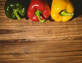 stock photo of pepper  - Three peppers on chopping board with copy space - JPG