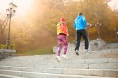 stock photo of upstairs  - Young couple of athlets running upstairs in the morning viewed from behind - JPG