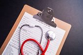 stock photo of medical chart  - Medical Chart and stethoscope isolated on black background - JPG