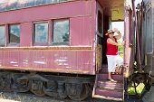 picture of bon voyage  - Elderly woman in trendy summer clothing standing waving at the camera from the steps of a vintage train carriage in a conceptual image of travel and vacations - JPG