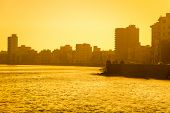 stock photo of malecon  - Colorful surise in Havana with a view of the malecon seawall and the city skyline - JPG