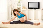 pic of pregnancy exercises  - Young beautiful pregnant woman doing stretching exercise - JPG