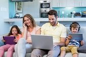 picture of couch  - Happy family on the couch together using devices at home in the living room - JPG