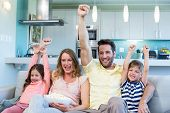 stock photo of couch  - Happy family on the couch watching tv at home in the living room - JPG