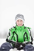 foto of kneeling  - Young boy kneeling in the snow making snowballs in his gloved hands looking at the camera with a friendly smile close up view in fresh white winter snow - JPG