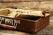 picture of old suitcase  - Old wooden suitcase with old books on wooden background - JPG