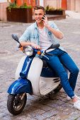 image of vespa  - Cheerful young man sitting on scooter and talking on the mobile phone - JPG