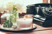 picture of copper  - Bouquet of white flowers in a vase, candles on a copper vintage tray, old rotary phone, retro home decor