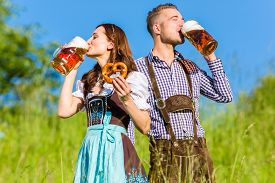 foto of pretzels  - German couple in Tracht with beer and pretzel - JPG