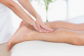 image of physiotherapist  - Physiotherapist doing calf massage to her patient in medical office - JPG