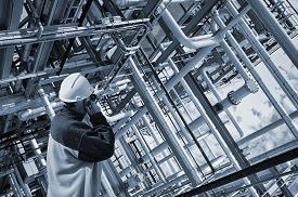 stock photo of pipeline  - oil worker pointing at giant pipelines construction inside refinery details - JPG