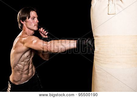 Young adult martial artist with heavy bag. Studio shot over black.