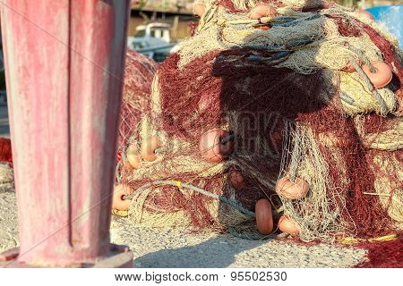 Heap of fishing net with red floats on Greek Vathys bay pier
