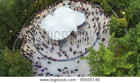 RUSSIA, MOSCOW - MAY 17, 2014: Many people dance on dancing ground in Sokolniki park at spring evening. Aerial view