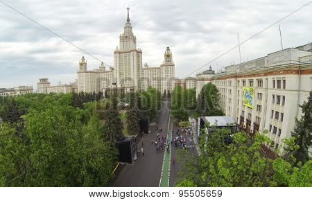 RUSSIA, MOSCOW - MAY 17, 2014: Main building of Moscow State University and students celebrate Day of Physicist near stage in front of Faculty of Physics. Aerial view.