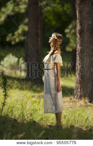 Vertical photo of beautiful young boho woman standing in forest with dramatic sunlight