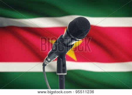 Microphone On Stand With National Flag On Background - Suriname