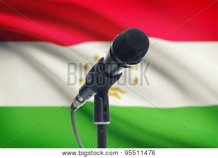 Microphone On Stand With National Flag On Background - Tajikistan