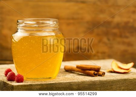 Glass Jar Of Linden Honey With Drizzler, Cinnamon, Raspberries, Apples On Wooden Background
