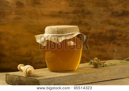 Glass Jar Of Honey With Drizzler, Jute Fabric, Dried Flowers On Wooden Background