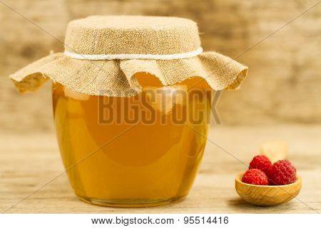 Glass Jar Of Honey Closed Jute Cloth And Raspberries On Wooden Background