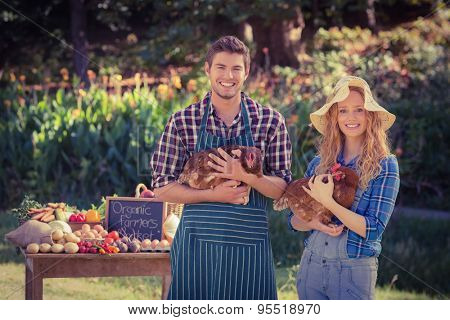 Happy farmers standing at their stall and holding chicken on a sunny day
