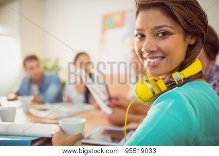Close up plan of a smiling businesswoman with yellow headphones in a meeting