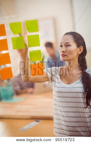 Concentrated businesswoman pointing post its on the wall in the office