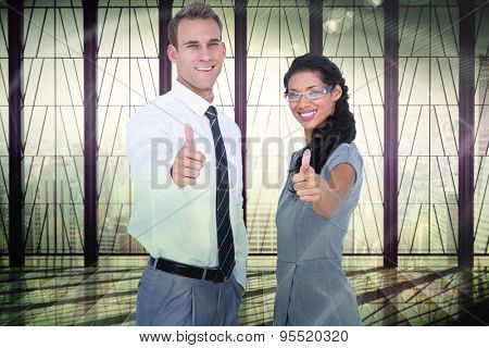 Happy business people looking at camera with thumbs up against window overlooking city