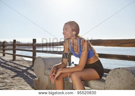 Young Female Jogger Resting On The Coastline