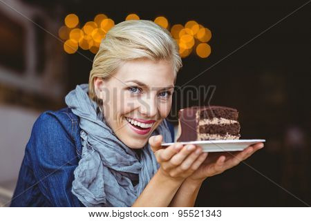 Smiling blonde holding a chocolate cake while looking at the camera