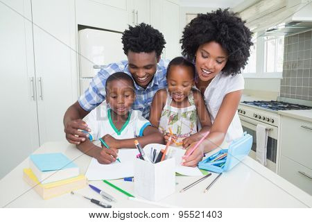 Happy parents helping children with homework at home in the kitchen
