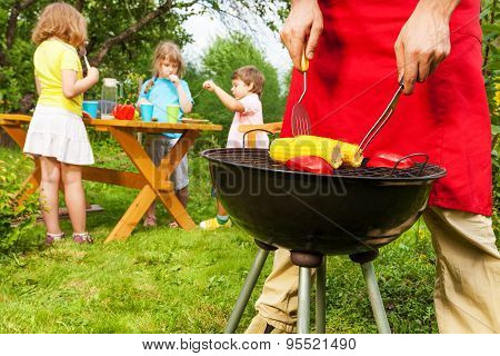 View of woman in apron fragment grilling corn