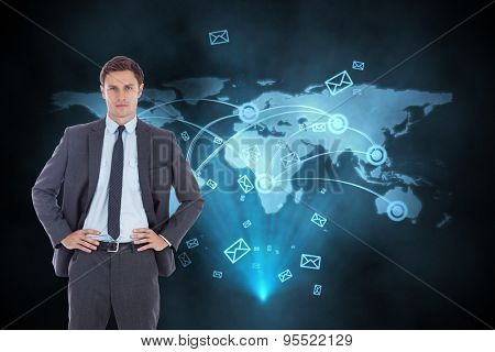 Serious businessman with hands on hips against futuristic technology interface