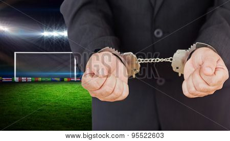 Handcuffed businessman against football pitch with lights and flags