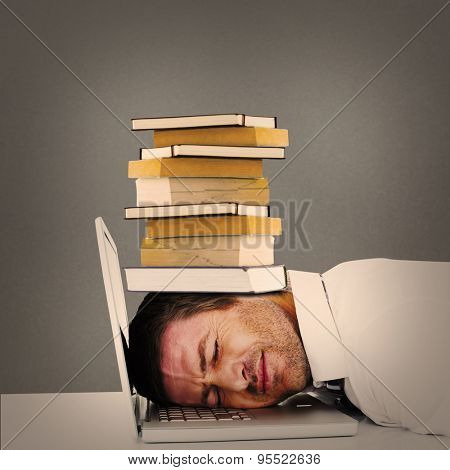 Tired businessman resting on laptop against grey background