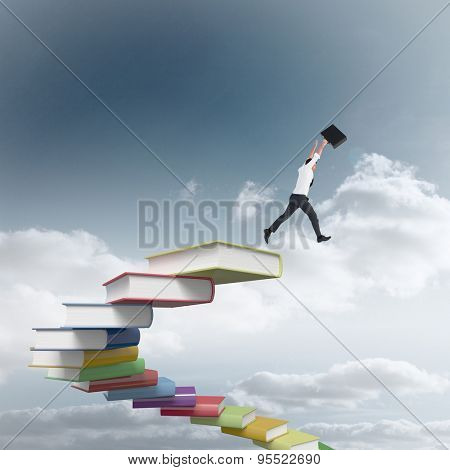 Businessman leaping with his briefcase against cloudy sky background