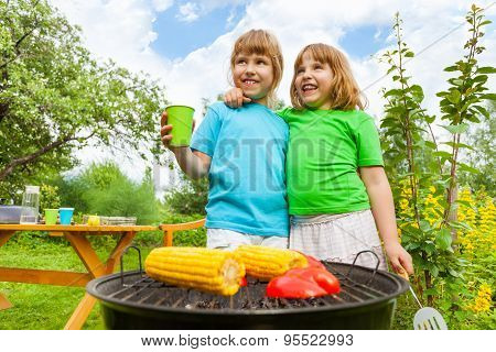 Close-up of sisters grilling corn with paprika