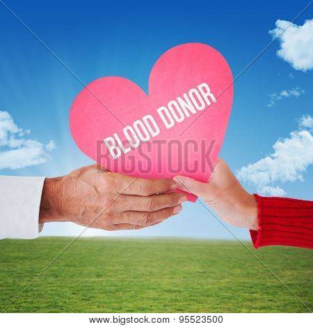 Couple holding heart against sky and field