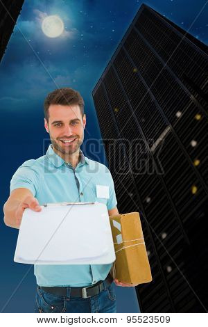 Delivery man with package giving clipboard for signature against city at night