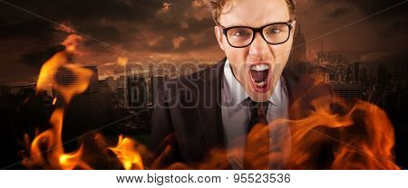 Young angry businessman shouting at camera against stormy sky over city