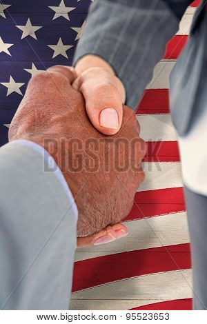 Businessman shaking hands with a co worker against pale grey wooden planks